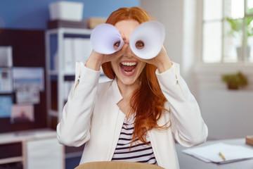 lachende geschäftsfrau schaut durch papierrollen