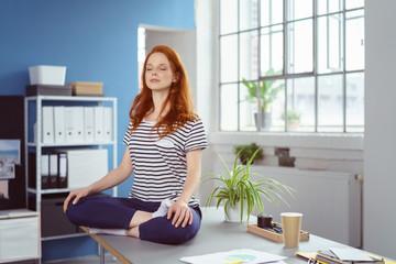 frau praktiziert yoga im büro