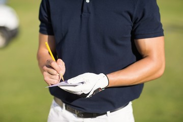 Midsection of golfer writing on score card