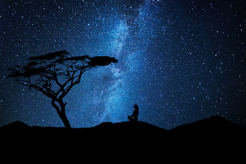 Woman silhouette near a tree meditates under a sky full of stars galaxy