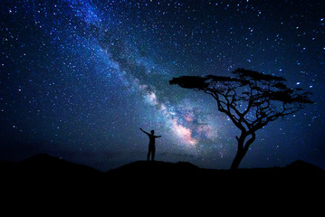 Man silhouette admiring the milky way galaxy near a tree
