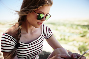 Close-up of beautiful young female in stylish sunglasses texting message on her smart phone. Pretty woman networking outdoors in summer day.