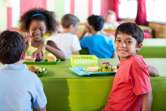 Boy with classmates having meal