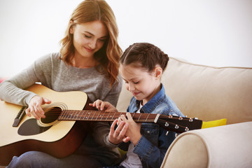 Small girl learning play guitar with teacher