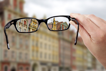 Hand holding glasses to see clearly