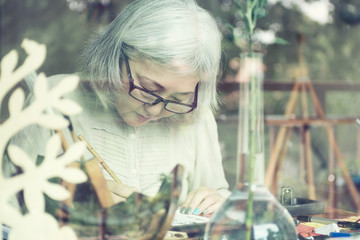 Asian senior woman painting at her home studio, view through win