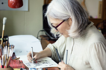 Asian senior woman artist sketching