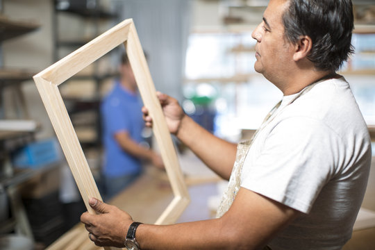 Man looking at wooden frame for canvas preparation in workshop