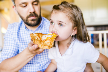 Father feeding his little daughter with pizza