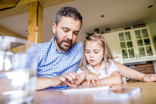 Father and daughter sitting at home using digital tablet