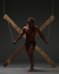 Sexual naked man, muscular, hands tied rope to wooden beams