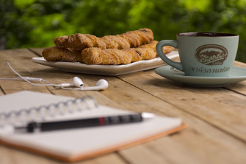 Breadstick golden brown with coffee and notebook and earphone with background of nature outdoor view.Backgroud work and relax.