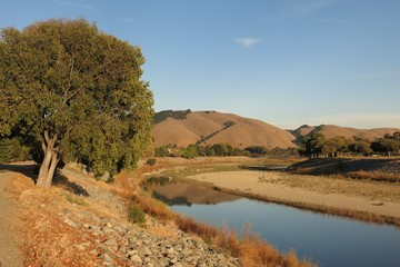 Northern California golden hills reflected in Alameda Creek, Fremont, California