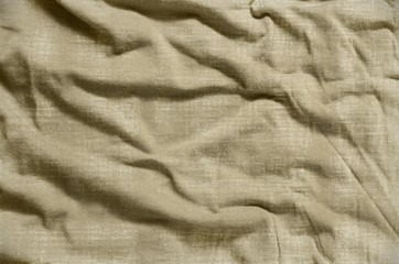 Bright brown wrinkled fabric texture. Close-up of soft cotton cloth, may be used as background.