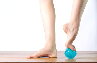 ballet dancer massage the forefoot with a ball