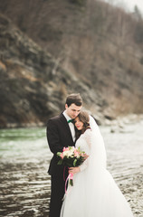 Happy wedding couple, bride and groom posing neat river against backdrop of the mountains