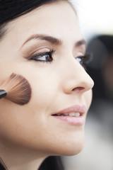 Beautiful latin woman applying makeup with brush