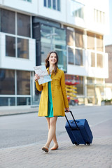 happy young woman with travel bag and map in city