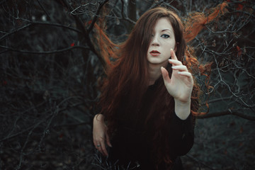 Red hair woman in desolate forest