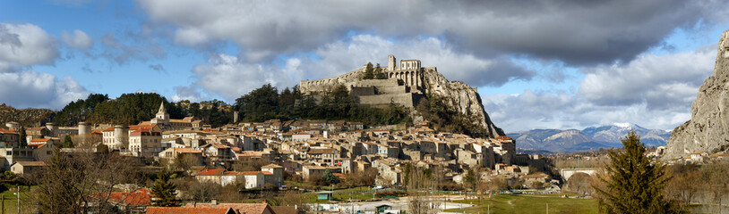 Panoramic view of Sisteron rooftops and the Citadel in summer light with clouds. The Sisteron Citadel and its fortifications is located in the Southern Alps (Alpes de Haute Provence), France