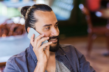 happy man calling on smartphone at bar or pub