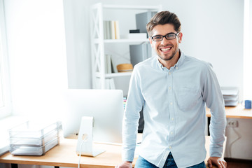 Smiling young businessman in glasses standing in office