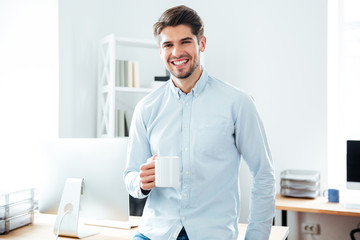Smiling young businessman drinkig coffee in office