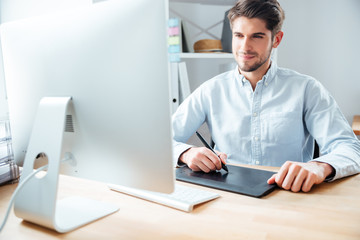 Man designer working using computer and graphic tablet at workplace