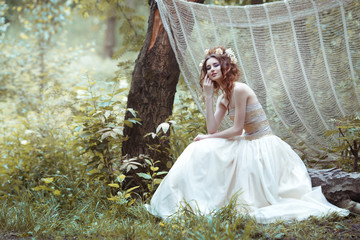 Girl with hairstyle decorated with flowers and a long light dress sidin on a fallen tree in the forest