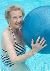 Active senior woman in the pool, doing exercises