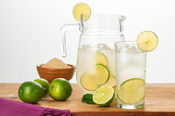 Pitcher and glass of cold lemonade with fresh lemons.