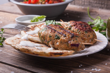 Kofta with flatbread on plate with salad