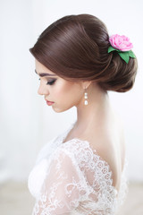 Portrait of a beautiful brunette bride with make-up and hairstyle in lace top view