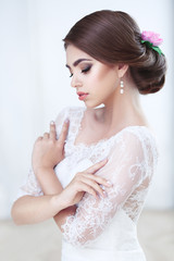 Portrait of a beautiful brunette bride bright makeup and hairstyle in lace dress