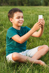 Young boy with a phone on the grass