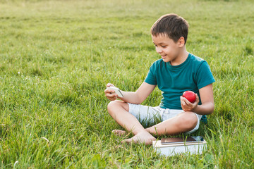 Young boy with a phone and apple on the grass