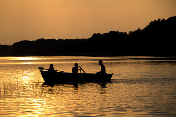 rowing wooden boat near forest in late evening during sunset