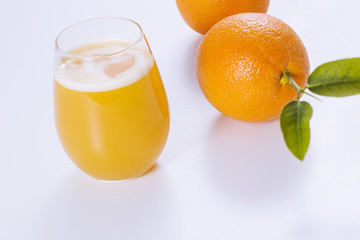 Fresh oranges and glass of orange juice.