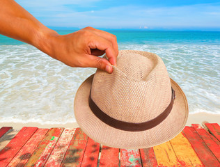 Man hand showing hold hat at the beautiful beach.