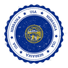 Nebraska flag badge. Grunge rubber stamp with Nebraska flag. Vintage travel stamp with circular text, stars and USA state flag inside it. Vector illustration.