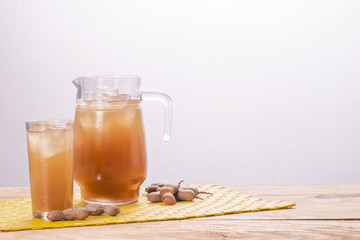Pitcher and glass of tamarind beverage.