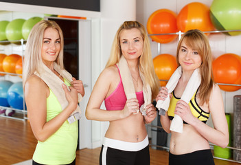 Happy girlfriends group posing in fitness club