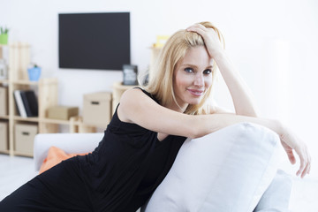Portrait of beautiful blonde woman sitting on a couch in her living room