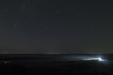 Summer night sky high above the plain. Single distant car lights at night meadow with clear starry sky.