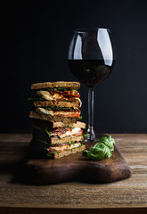Caprese sandwich or panini and glass of red wine. Whole grain bread, mozzarella, dried tomatoes, basil. Dark background, vertical composition