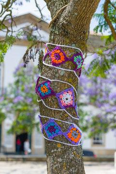 Yarn bombing in trees. European park.