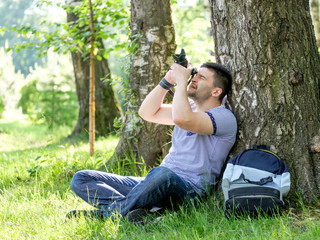 Portrait of young hipster man with camera outdoors. Young male photographer photographing nature on summer day.