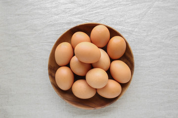 Eggs in wooden bowl on linen background