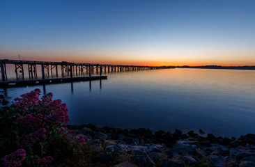 Silhouette of pier and hills with beautiful sunset