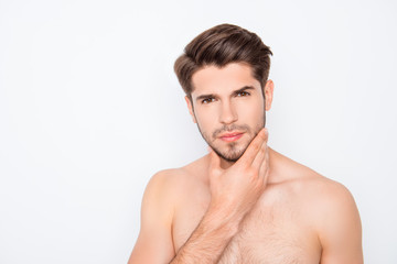 Handsome young man expertising his face before shaving